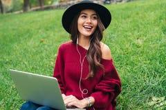 一个快乐的亚裔女孩的画象耳机的使用膝上型计算机 免版税库存照片