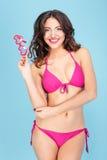 一个快乐的俏丽的女孩的画象拿着镜片的泳装的 免版税库存照片