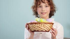 一个快乐的卷曲红发男孩的画象有复活节篮子的在蓝色背景的手上 股票录像