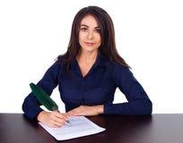 一个快乐的女商人的画象坐她的书桌和报名参加在白色背景的合同 库存照片