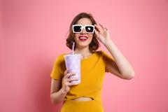一个快乐的女孩的画象拿着杯子的太阳镜的 库存照片