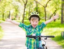 一个快乐的孩子的画象一辆自行车的在夏天公园 免版税图库摄影