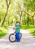 一个快乐的孩子的画象一辆自行车的在夏天公园 免版税库存照片