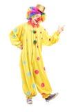 一个快乐的小丑的全长画象一套黄色服装的 库存照片