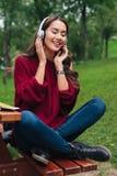 一个快乐的微笑的亚裔女孩的画象耳机的 免版税库存照片