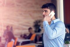 一个快乐的微笑的人办公室工作者的画象谈话在手机,当站立在现代办公室空间时 免版税库存图片