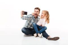 一个快乐的父亲和他的小女儿的画象 免版税库存照片