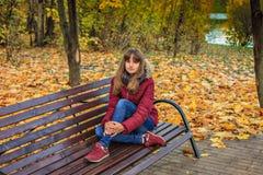 一个快乐的红发女孩坐长凳和梦想 库存图片