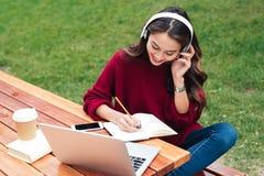 一个快乐的聪明的亚裔女孩的画象耳机学习的 免版税库存图片
