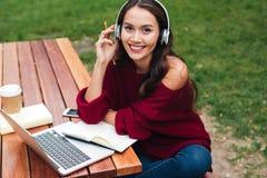 一个快乐的聪明的亚裔女孩的画象耳机学习的 库存照片