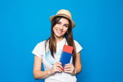 一个快乐的逗人喜爱的女孩旅行家的画象在夏天给显示与票的护照穿衣到照相机被隔绝在蓝色背景 库存照片