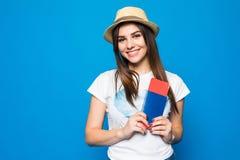 一个快乐的逗人喜爱的女孩旅行家的画象在夏天给显示与票的护照穿衣到照相机被隔绝在蓝色背景 免版税图库摄影