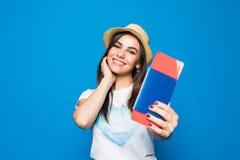 一个快乐的逗人喜爱的女孩旅行家的画象在夏天给显示与票的护照穿衣到照相机被隔绝在蓝色背景 图库摄影