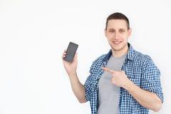 一个快乐,正面,可爱的人的画象有发茬的在一件衬衣,有有一个黑屏幕的一个智能手机的在他的手上,点 免版税库存照片