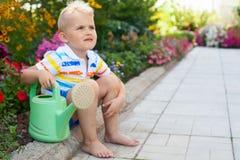 一个快乐,被晒黑的白肤金发的男孩由与双桅船的花床坐 免版税库存照片