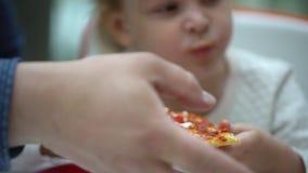 一个快餐咖啡馆的一个小孩子吃薄饼 逗人喜爱的小孩女孩画象滑稽吃在购物中心的快餐法院 股票视频