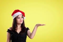 一个快活的女孩的圣诞节介绍在黄色背景的 免版税库存照片