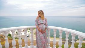 一个怀孕的女孩在阳台站立在海旁边并且爱抚她的肚子 4K 影视素材