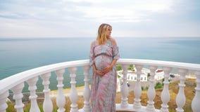 一个怀孕的女孩在阳台站立在海旁边并且爱抚她的肚子 4K 股票视频