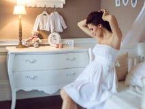 一个怀孕的女孩的画象一件白色礼服的在家庭内部 免版税库存照片