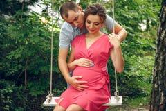 一个怀孕的少妇和她的丈夫 一个愉快的家庭坐摇摆,握腹部 公园怀孕的松弛妇女 免版税库存照片