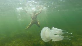 一个怀孕的快乐的少妇游泳并且潜水在与一只白色水母的水下在公海 股票视频