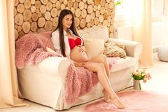 一个怀孕的美好的女孩立场在屋子浅粉红色里坐 免版税库存图片