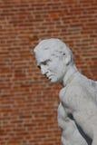 一个思想家字符的雕象与砖的在背景 库存照片
