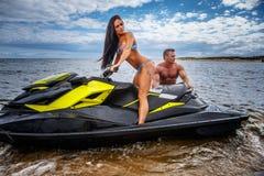 一个性感的女孩和赤裸上身的肌肉男性的有吸引力的夫妇获得与喷气机滑雪的乐趣在海岸 免版税库存图片