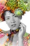 一个性感的美丽的非裔美国人的女孩的画象有一种非洲的发型的,与异乎寻常的植物doble曝光她的 免版税库存照片