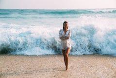 一个性感的被晒黑的美丽的欧洲女孩在沙子站立反对高泡沫似的波浪背景,拥抱自己与 免版税库存图片