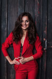一个性感的年轻企业夫人的画象一套红色衣服的在黑暗的木背景 免版税图库摄影