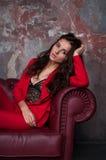 一个性感的年轻企业夫人的画象一套红色衣服的在黑暗的s 免版税库存图片