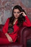 一个性感的年轻企业夫人的画象一套红色衣服的在黑暗的s 免版税库存照片