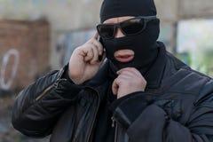 一个恐怖分子、一位匪盗一黑皮夹克的和面具谈话在电话 免版税库存图片