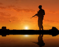 一个恐怖分子的剪影有一个武器的在河附近的日落 图库摄影