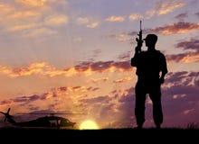 一个恐怖分子的剪影有武器的在直升机附近 免版税图库摄影