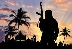 一个恐怖分子的剪影有武器的 免版税库存图片
