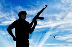 一个恐怖分子的剪影有武器的 库存图片