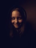 一个恶魔青少年的女孩的画象有阴险微笑的 免版税库存图片