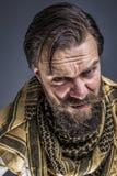 一个恼怒的人的特写镜头画象有佩带traditiona的胡子的 免版税库存照片
