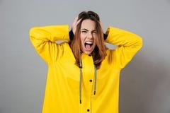 一个恼怒的女孩的画象在雨衣穿戴了 免版税库存图片