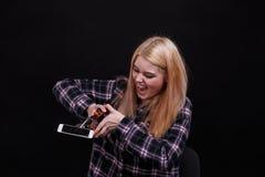 一个恼怒的女孩,断裂在建筑夹子帮助下的一个智能手机 在黑色背景 库存图片