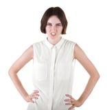 一个恼怒的女孩 恶心的女孩用在臀部的手 在白色背景隔绝的女性 女衬衫的一个深色的少妇 免版税库存照片