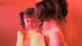 一个恼怒的孩子在镜子看 一件黄色礼服的一个美丽的小女孩对在镜子的舱口盖是恼怒 有尾标的女孩 股票视频