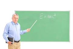一个恼怒的成熟教师和黑板 免版税库存图片