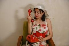 一个恼怒的深色头发的女孩由电话谈话 库存图片