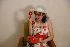 一个恼怒的深色头发的女孩由电话谈话 免版税图库摄影