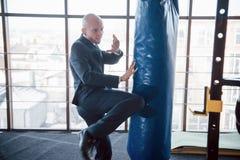 一个恼怒的秃头商人搅拌在健身房的拳击梨 愤怒管理的概念 库存照片