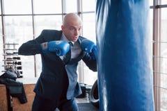 一个恼怒的秃头商人搅拌在健身房的拳击梨 愤怒管理的概念 图库摄影